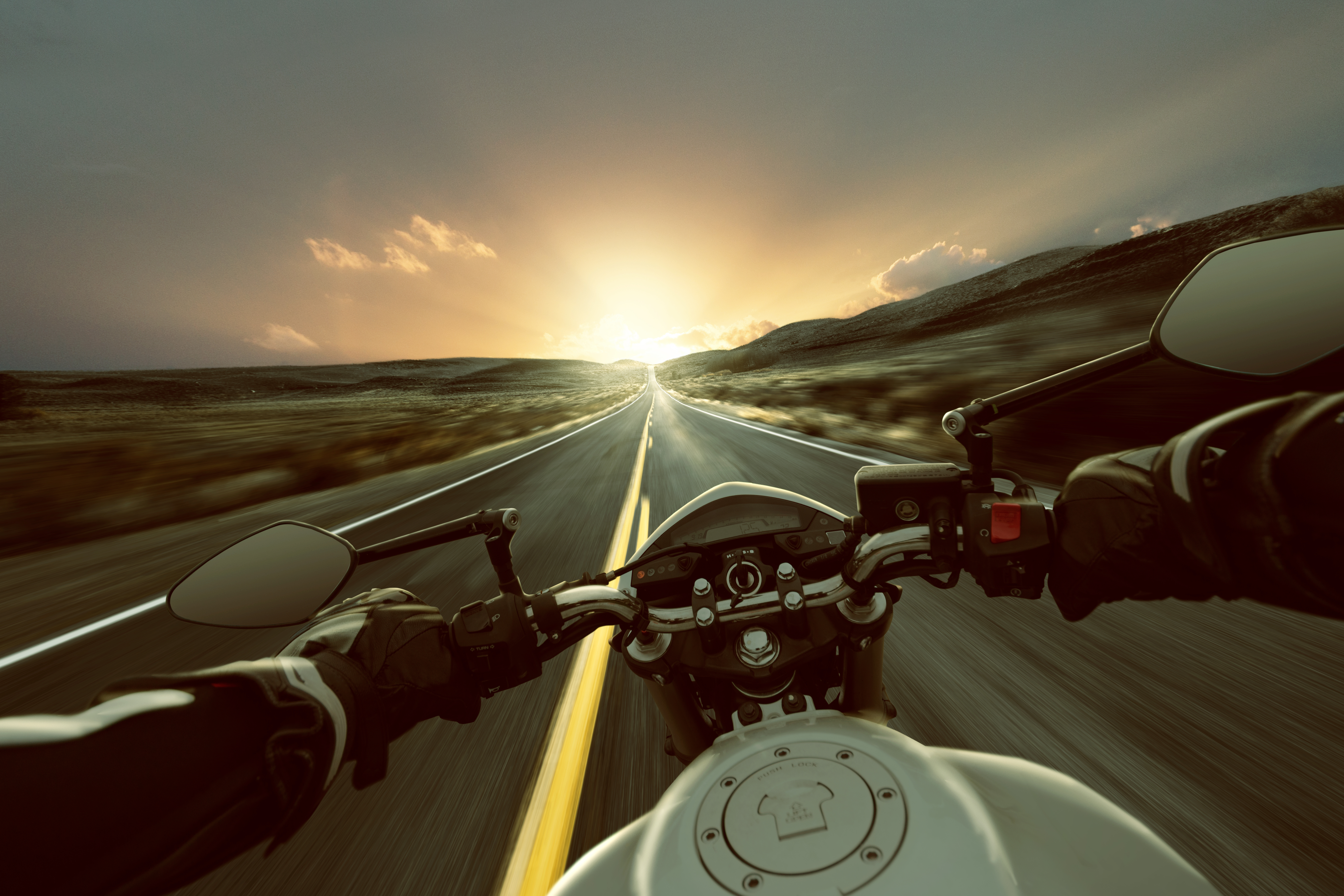 Une moto lancée sur une ligne droite sur fond de coucher de soleil